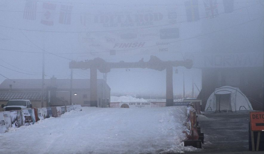 CORRECTS YEAR FROM 2017 TO 2016 Fog obscures the burled arch over the finish line of the Iditarod Trail Sled Dog Race in Nome, Alaska, on Thursday, March 17, 2016. Eighty-five mushers began the nearly 1,000-mile race to Nome from Anchorage on March 6. As of Thursday morning, 43 mushers had reached Nome, 13 have scratched and 29 remain on the trail. (AP Photo/Mark Thiessen)