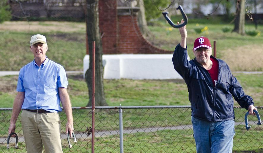 Neil Sweigart, looks on as Duane Coan pitches his horseshoe in the horseshoe pits at Gregg Park Friday, March 12, 2016, in Vincennes, Ind. These men are attempting to revitalize an old past time in Knox County by creating the Vincennes Horseshoe Pitching League. They have set up a Facebook page with the title of the league if anyone is interested in joining. (Kevin J. Kilmer/Sun-Commercial via AP) MANDATORY CREDIT