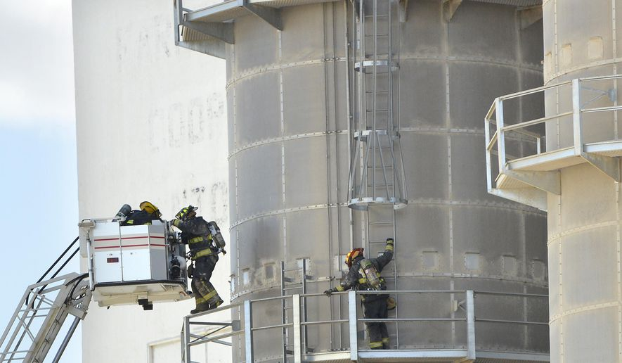 Firefighters make their way back to an aerial ladder truck while inspecting an elevator after an explosion at the Central Valley Ag Cooperative grain elevator in Hinton, Iowa, Thursday, March 17, 2016. The explosion shoot the entire town, according to witnesses. (Tim Hynds/Sioux City Journal via AP)