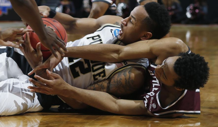 Purdue forward Vince Edwards, top, fights for control of a loose ball with Arkansas Little Rock forward Mareik Isom in the first half of a first-round men's college basketball game Thursday, March 17, 2016, in the NCAA Tournament in Denver. (AP Photo/David Zalubowski)