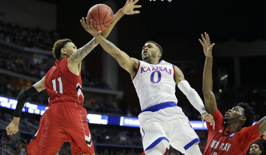Kansas guard Frank Mason III, center, drives to the basket between Austin Peay defenders Khalil Davis, left, and Kenny Jones, right, during the first half of a first-round men's college basketball game in the NCAA Tournament, Thursday, March 17, 2016, in Des Moines, Iowa. (AP Photo/Charlie Neibergall)