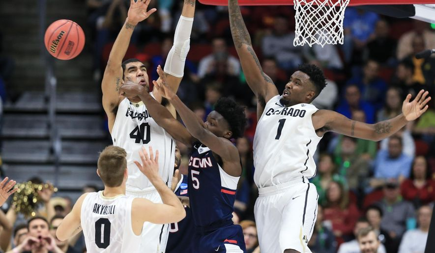 Connecticut's Daniel Hamilton (5) passes the ball while being defended by Colorado's Josh Scott (40), Wesley Gordon (1) and Thomas Akyazili (0), during a first-round men's college basketball game in the NCAA Tournament in Des Moines, Iowa, Thursday, March 17, 2016. (AP Photo/Nati Harnik)