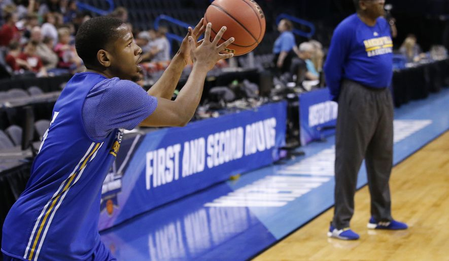 Cal State Bakersfield guard Dedrick Basile, left, grabs a pass during a practice for a first round men's college basketball game in the NCAA Tournament, Thursday, March 17, 2016, in Oklahoma City. Head coach Rod Barnes is at right. (AP Photo/Sue Ogrocki)