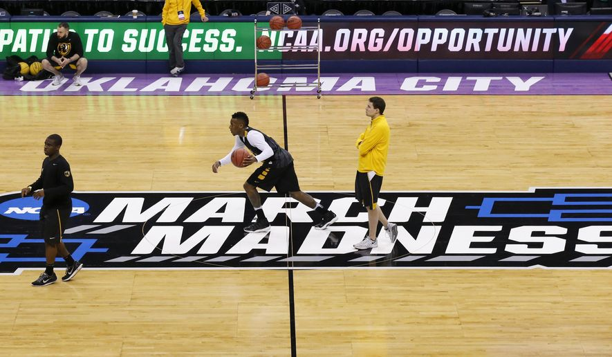 Virginia Commonwealth guard Melvin Johnson, center, dribbles across the court as head coach Will Wade, right, watches, during a practice for a first round men's college basketball game in the NCAA Tournament, Thursday, March 17, 2016, in Oklahoma City, Okla. (AP Photo/Sue Ogrocki)