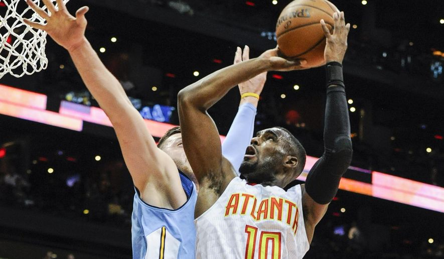 Atlanta Hawks guard Tim Hardaway Jr. (10) goes to the basket against the defense of Denver Nuggets center Jusuf Nurkic, of Bosnia, during the first half of an NBA basketball game, Thursday, March 17, 2016, in Atlanta. (AP Photo/John Amis)