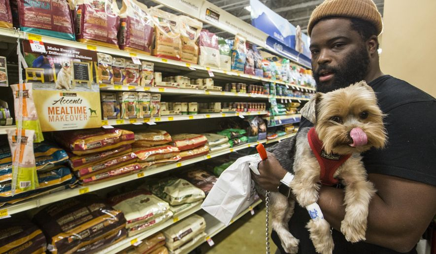 In this Wednesday, March 16, 2016, photo, pet owner Tron Oliver holds Rocket, his York terrier, after filling a veterinarian prescription at the PetSmart Midtown store in Los Angeles. Americans spent just over $60 billion on their pets in 2015, a record fueled by a big jump in what owners shelled out for services like grooming, boarding and training. (AP Photo/Damian Dovarganes)