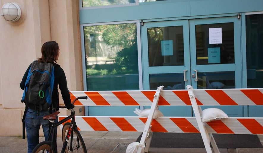 A woman reads a sign informing people a building is closed on the University of Hawaii at Manoa campus in Honolulu on Thursday, March 17, 2016. A 29-year-old visiting researcher was taken to a hospital with serious injuries after an explosion at a laboratory in the building. (AP Photo/Audrey McAvoy)