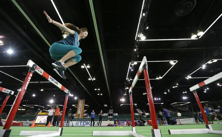 Sprinter Bianca Razor, of Romania, jumps over a hurdle, Wednesday, March 16, 2016, the day before the start of the World Indoor Athletics Championships in Portland, Ore. (AP Photo/Elaine Thompson)
