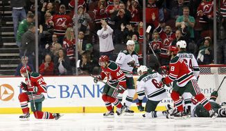 New Jersey Devils right wing Devante Smith-Pelly, left, celebrates after scoring a goal on Minnesota Wild goalie Devan Dubnyk (40) during the first period of an NHL hockey game, Thursday, March 17, 2016, in Newark, N.J. (AP Photo/Julio Cortez)