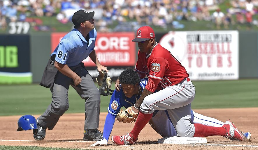 Kansas City Royals' Raul Mondesi reaches third under Los Angeles Angels third baseman Jefry Marte on a triple during the third inning of a spring training baseball game Friday, March 18, 2016, in Surprise, Ariz. The Royals won 7-4. (John Sleezer/The Kansas City Star via AP)