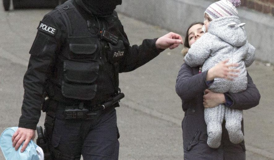Police evacuate a woman and a small child during a police raid in the Molenbeek neighbourhood of Brussels, Belgium in this file photo from on Friday, March 18, 2016. On June 25, 2016, anti-terror officials arrested two individuals in early-morning raids. Authorities say there is no connection to the March 22 terror attack in Belgium. (AP Photo/Geoffrey Van der Hasselt)
