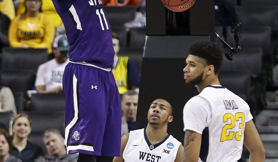 Stephen F. Austin's Clide Geffrard, Jr. (11) dunks the ball as West Virginia's Esa Ahmad (23) and Jevon Carter (2) react during the first half of a first-round men's college basketball game in the NCAA Tournament,Friday, March 18, 2016, in New York. (AP Photo/Frank Franklin II)