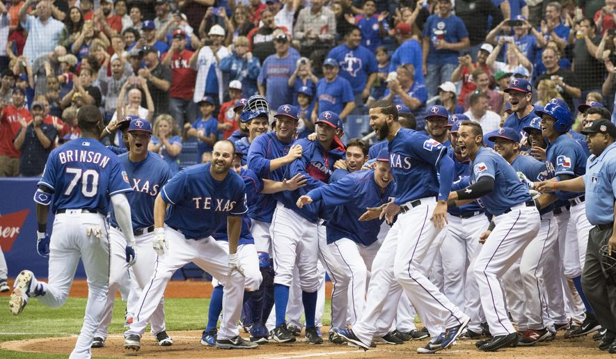 Texas Rangers' Lewis Brinson (70) celebrates his winning home run with teammates as he runs to home plate in the bottom of the ninth inning during a spring exhibition baseball game against the Kansas City Royals, Friday, March 18, 2016, in San Antonio. (AP Photo/Darren Abate)