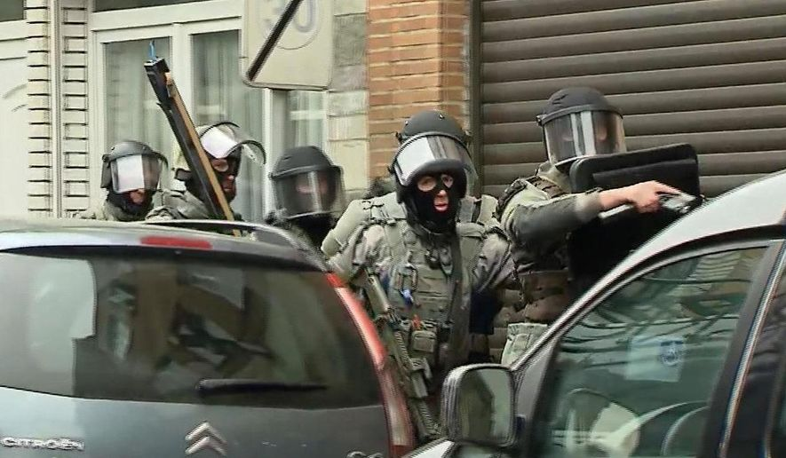 In this framegrab taken from VTM, armed police officers take part in a raid in the Molenbeek neighborhood of Brussels, Belgium, Friday March 18, 2016. After an intense four-month manhunt across Europe and beyond, police on Friday captured Salah Abdeslam, the top fugitive in the Paris attacks in the same Brussels neighborhood where he grew up. (VTM via AP) BELGIUM OUT