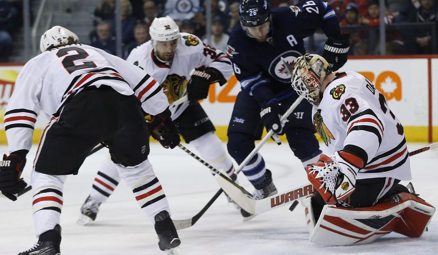 Chicago Blackhawks' goalie Scott Darling (33) saves a shot by Winnipeg Jets' Blake Wheeler (26) as Blackhawks' Duncan Keith (2) and Michal Rozsival (32) also defend during second-period NHL hockey game action in Winnipeg, Manitoba, Friday, March 18, 2016. (John Woods/The Canadian Press via AP) MANDATORY CREDIT
