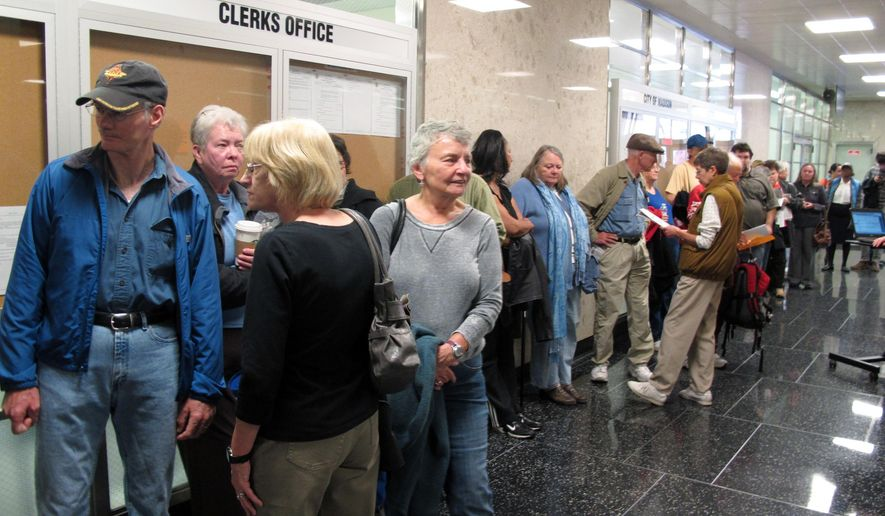 FILE - In this Oct. 22, 2012 file photo, voters line up outside the Madison city clerk's office to be among the first to cast ballots early for the Nov. 6 2012 presidential election in Madison, Wis. Voters in Wisconsin can begin casting ballots in the 2016 presidential primary race on Monday, March 21, 2016 a little over two weeks before the state's April 5 primary. (AP Photo/Scott Bauer)