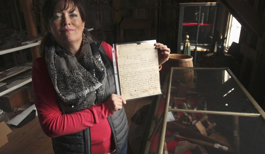 In this Feb. 18, 2016 photo, Carolyn Ware stands in the education area of the Golden Windmill in Golden, Ill., as she holds an 1897 letter written from a customer in Barbados to the proprietor of the windmill concerning the market for flour. Ware recently found several old letters, market reports and receipts dating from the late 1800s while cleaning out the attic of her father's home in Clayton, Ill. The letters were sent from mill customers around the world. (Phil Carlson/The Quincy Herald-Whig via AP) MANDATORY CREDIT