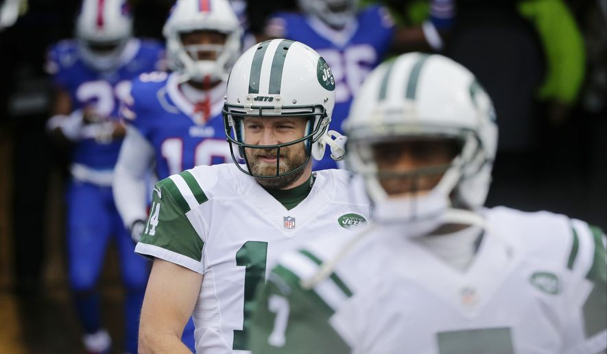 FILE - In this Jan. 3, 2016, file photo, New York Jets quarterback Ryan Fitzpatrick (14) and teammate Geno Smith (7) walk on the field to warm up before an NFL football game against the Buffalo Bills in Orchard Park, N.Y. New York Jets general manager Mike Maccagnan says the team remains focused on trying to re-sign quarterback Ryan Fitzpatrick, although it also has contingency plans. (AP Photo/Bill Wippert, File)