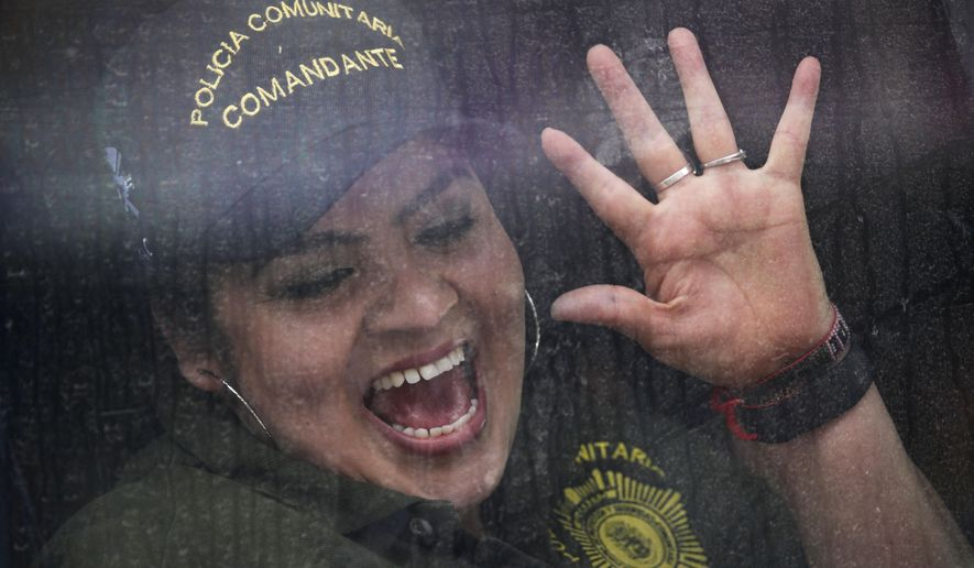 Community police force leader Nestora Salgado, waves from inside a bus as she leaves the Tepepan prison after courts threw out charges of homicide and kidnapping in Mexico City, Friday, March 18, 2016.  Salgado, who has dual U.S. and Mexican citizenship, returned to Mexico in 2004 and joined one of the community police forces in Olinala, a town about 110 miles (180 kilometers) south of Mexico City. While legal, the community police forces have often had a troubled relationship with state and federal authorities. She was arrested in August 2013 after people who had been detained by the force filed a complaint of kidnapping. (AP Photo/Marco Ugarte)