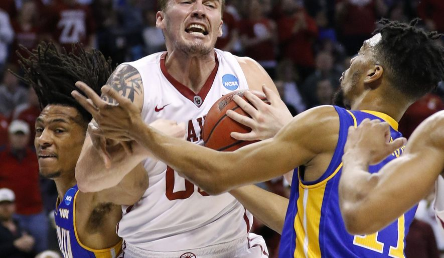 Oklahoma forward Ryan Spangler, center, grabs a rebound between Cal State Bakersfield forward Matt Smith, left, and forward Jaylin Airington, right, in the first half of a first-round men's college basketball game in the NCAA Tournament, Friday, March 18, 2016, in Oklahoma City. (AP Photo/Alonzo Adams)