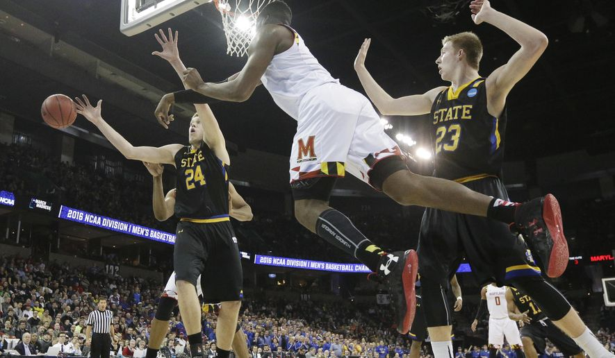 Maryland forward Robert Carter, center, passes the ball around South Dakota State forward Mike Daum (24) and forward Logan Doyle (33) during the second half of a first-round men's college basketball game in the NCAA Tournament in Spokane, Wash., Friday, March 18, 2016. Maryland won 79-74. (AP Photo/Young Kwak)