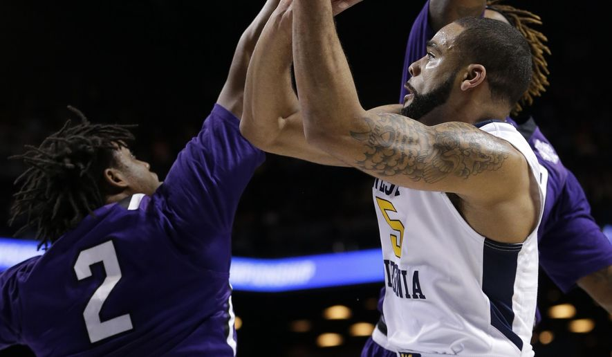 West Virginia's Jaysean Paige (5) shoots over Stephen F. Austin's C.J. Williams (2) during the first half of a first-round men's college basketball game in the NCAA Tournament,Friday, March 18, 2016, in New York. (AP Photo/Frank Franklin II)