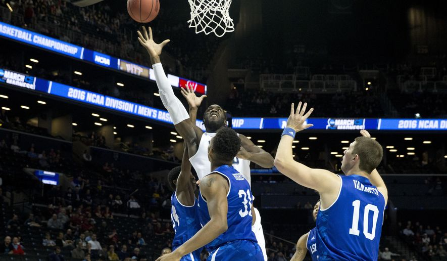Villanova forward Daniel Ochefu, center, goes to the basket against UNC Asheville forward Sam Hughes (31) and guard Kevin Vannatta (10) during the first half of a first-round men's college basketball game in the NCAA Tournament, Friday, March 18, 2016, in New York. (AP Photo/Mary Altaffer)
