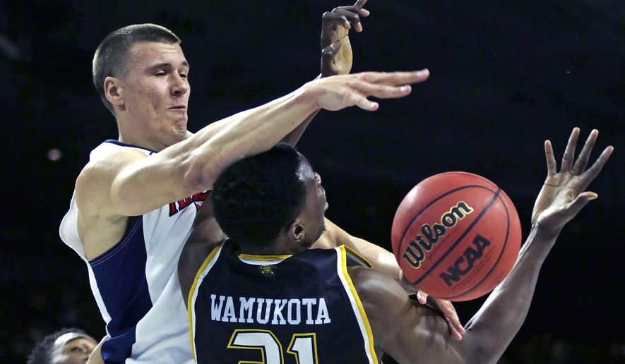 Arizona center Kaleb Tarczewski, left, covers Wichita State center Bush Wamukota (21), who tries to grab a rebound during the first half of a first-round of the NCAA college men's basketball tournament in Providence, R.I., Thursday, March 17, 2016. (AP Photo/Charles Krupa)