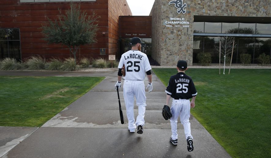 "FILE - In this Feb. 28, 2015, file photo, Chicago White Sox's Adam LaRoche, left, and his son Drake walk to the White Sox's clubhouse during a photo day before a baseball spring training workout in Phoenix. Kudos to Adam LaRoche for wanting to spend time with his son, and walking away from a $13 million salary to make sure that happened. But there's nothing wrong with the White Sox telling the now-retired first baseman that ""Bring Your Child To Work Day"" couldn't be every day. (AP Photo/John Locher, File)"