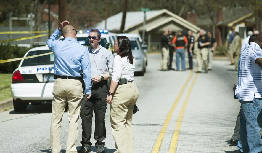 Police officers work the scene of an officer-involved shooting Friday, March 18, 2016, in Greenville, S.C.  A South Carolina police officer was shot and killed Friday as he attempted to serve a warrant on a suspect who later killed himself, Greenville Police Chief Ken Miller said.  (Lauren Petracca/The Greenville News via AP) NO SALES; MANDATORY CREDIT