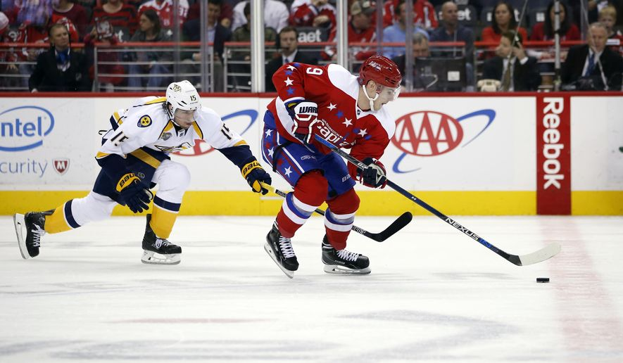 Nashville Predators center Craig Smith (15) reaches for the puck as Washington Capitals defenseman Dmitry Orlov (9), from Russia, skates with it during the first period of an NHL hockey game, Friday, March 18, 2016, in Washington. (AP Photo/Alex Brandon)