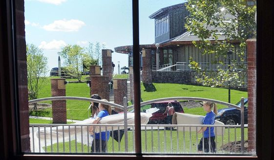 In this Aug. 27, 2010 photo, students walk past the Rocky Top Student Center as they move into the Crescent residence hall on the Quinnipiac University's York Hill campus in Hamden, Conn. Much as basketball put the University of Connecticut on the map, Quinnipiac officials say their national political polls have elevated the profile of the school, aiding its rise from a local college to a university that draws students from around the world. (Brad Horrigan/New Haven Register via AP)