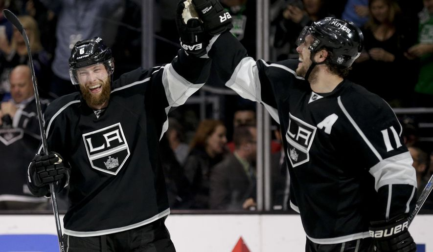 Los Angeles Kings center Anze Kopitar, right, celebrates his game-winning goal with defenseman Jake Muzzin during overtime in an NHL hockey game against the New York Rangers in Los Angeles, Thursday, March 17, 2016. (AP Photo/Chris Carlson)