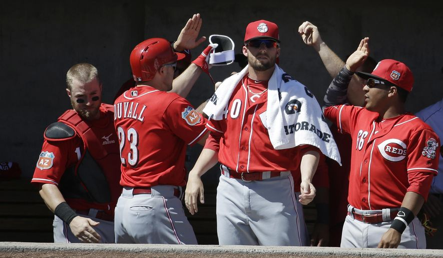 Cincinnati Reds' Adam Duvall (23) is congratulated by teammates after hitting a home run during the first inning of a spring training baseball game against the Milwaukee Brewers on Friday, March 18, 2016, in Phoenix. (AP Photo/Darron Cummings)