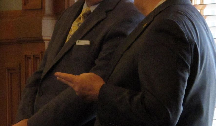 Tim Shallenburger, left, president of the Kansas Development Finance Authority, confers with state Rep. Jerry Lunn, R-Overland Park, as the House debates a bill giving legislators more oversight of debt financing for big construction projects, Friday, March 18, 2016, at the Statehouse in Topeka, Kan. The authority issues bonds and handles debt for state agencies. (AP Photo/John Hanna)