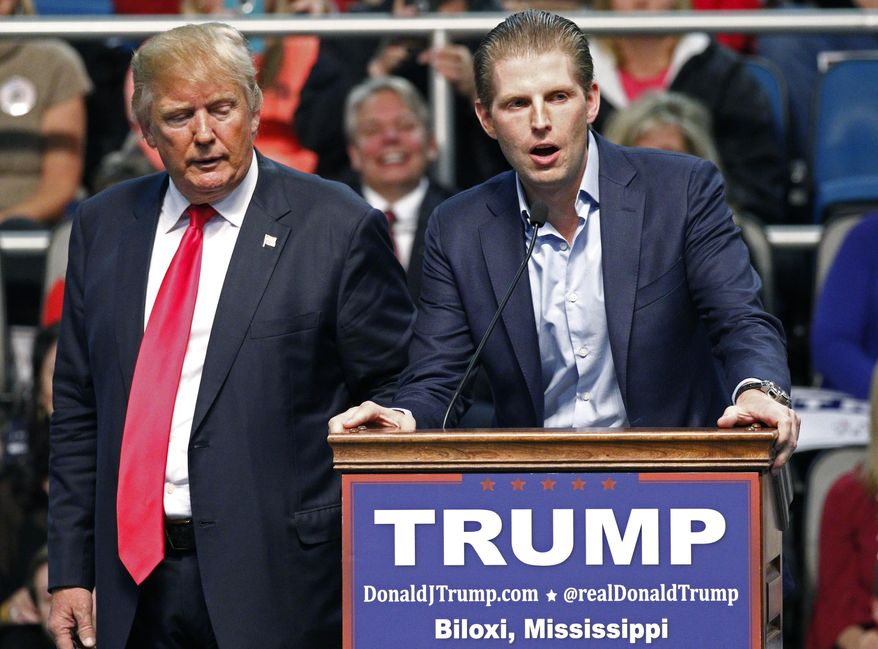 Republican presidential candidate Donald Trump, left, listens as his son Eric Trump speaks during a rally in Biloxi, Miss., in this Jan. 2, 2016, file photo. (AP Photo/Rogelio V. Solis) ** FILE **