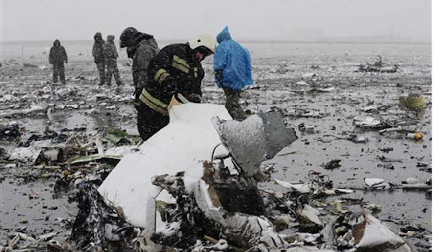 Russian Emergency Ministry employees investigate the wreckage of a crashed plane at the Rostov-on-Don airport, about 950 kilometers (600 miles) south of Moscow, Russia Saturday, March 19, 2016. A Dubai airliner crashed and caught fire early Saturday while landing in strong winds in the southern Russian city of Rostov-on-Don, officials said. (AP Photo)