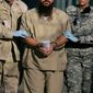 In this Dec. 6, 2006, file photo, reviewed by a U.S. Department of Defense official, a shackled detainee is transported away from his annual Administrative Review Board hearing with U.S. officials, in Camp Delta detention center at the Guantanamo Bay U.S. Naval Base in Cuba. (AP Photo/Brennan Llinsley, File)