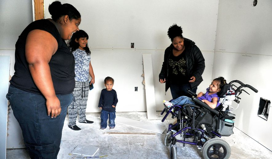 In this March 10, 2016 photo, Amari Prewitt, right, smiles as her mom Elena Williams, left, sister Aniya Lopez, brother Julian Prewitt,  and aunt Erica Williams show her the new bedroom she will be getting at their Habitat For Humanity House in Medford, Ore. (Denise Baratta /The Medford Mail Tribune via AP) MANDATORY CREDIT