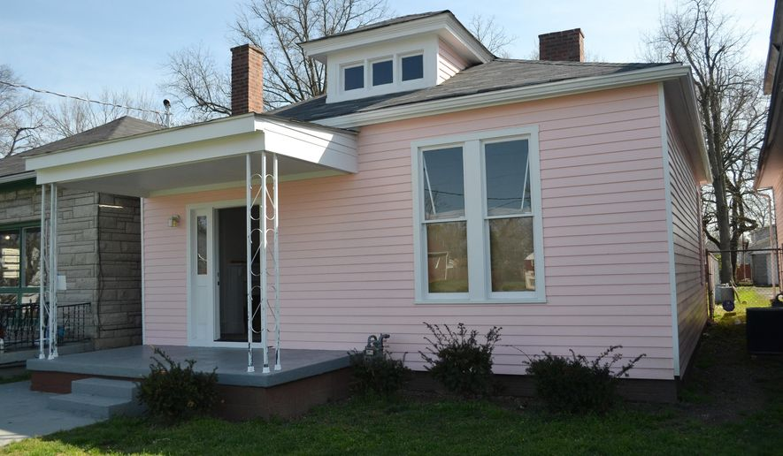 In this March 18, 2016 photo, the childhood home of Muhammad Ali is seen in Louisville, Ky. Two investors purchased the home and are restoring it to how it looked with Ali's family lived there, including its original pink color. (AP Photo/Dylan Lovan)