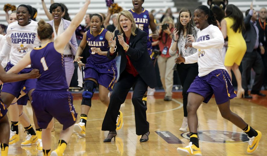 Albany head coach Katie Abrahamson-Henderson, center, and her players celebrate their 61-59 win over Florida in a first-round women's college basketball game in the NCAA Tournament on Friday, March 18, 2016, in Syracuse, N.Y. (AP Photo/Mike Groll)