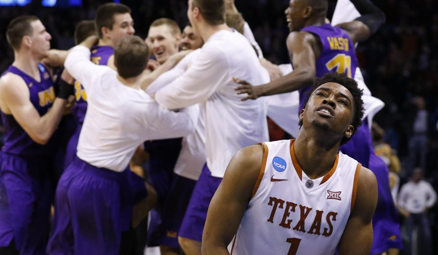 Texas guard Isaiah Taylor (1) reacts as the Northern Iowa team celebrates after guard Paul Jesperson made a last-second half-court shot to win the the first-round men's college basketball game in the NCAA Tournament in Oklahoma City, Friday, March 18, 2016. Northern Iowa won 75-72. (AP Photo/Alonzo Adams)