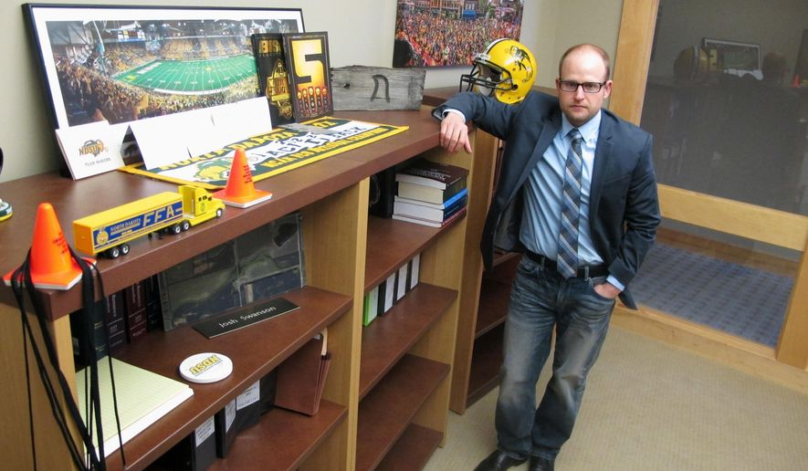 In this Friday, March 18, 2016 photo Fargo attorney Josh Swanson of Vogel Law Firm in Fargo, N.D. poses in his office next to a bookcase that contains numerous folders of legal cases he is handling in the oil patch of western North Dakota. Swanson says about 90 percent of his cases are based out of the Bakken oil formation, where the legal action is picking up as the oil activity decreases. (AP Photo/Dave Kolpack)