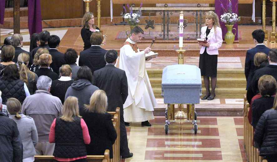 Rev. Andrew Kowalczyk, CSMA, sprinkles Holy Water as he blesses the casket of Doug Risse on Friday, March 18, 2016, at St. Clare of Montefalco Catholic Church in Grosse Pointe Park, Mich.  The church  held a funeral for Risse whose body was unclaimed at the morgue for six months after he died in a fire. (Todd McInturf/Detroit News via AP)  DETROIT FREE PRESS OUT; HUFFINGTON POST OUT; MANDATORY CREDIT
