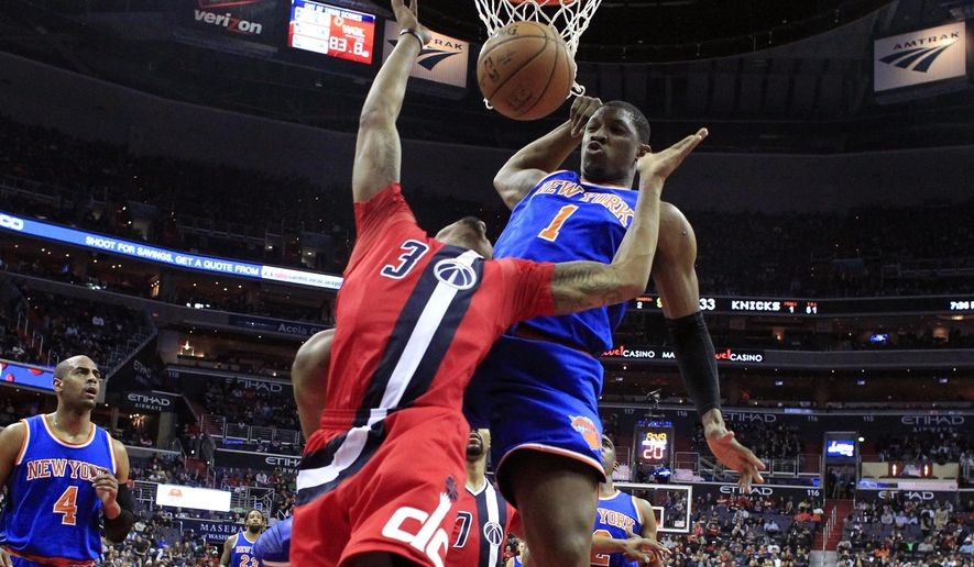 Washington Wizards guard Bradley Beal (3) has his shot blocked by New York Knicks center Kevin Seraphin (1), from France, during the first half of an NBA basketball game Saturday, March 19, 2016, in Washington. (AP Photo/Alex Brandon)