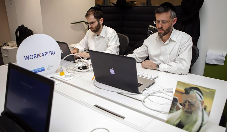 In this photo taken Tuesday, March 15, 2016, ultra-Orthodox Jewish men work at a high tech start-up in an office in Tel Aviv. More and more, young ultra-Orthodox insist they can continue to lead pious lives while also embracing technology, the modern workplace and their fellow Israelis.  (AP Photo/Dan Balilty)