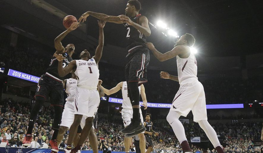 Saint Joseph's guard Shavar Newkirk (1) goes after a rebound against Cincinnati forward Octavius Ellis (2) and guard Farad Cobb, left, during the first half of a first-round men's college basketball game in the NCAA Tournament in Spokane, Wash., Friday, March 18, 2016. (AP Photo/Young Kwak)