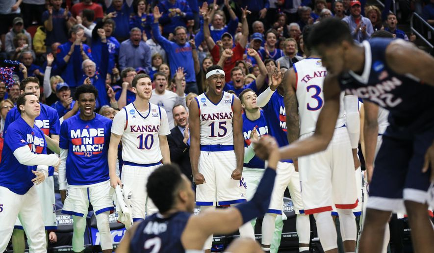 The Kansas bench cheers for Jamari Traylor (31) after he blocked a shot by Connecticut's Jalen Adams (2) during a second-round men's college basketball game in the NCAA Tournament in Des Moines, Iowa, Saturday, March 19, 2016. (AP Photo/Nati Harnik)