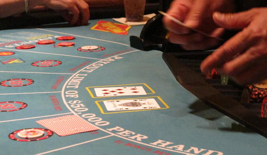 This March 9, 2016 photo shows a card game under way at the Tropicana casino in Atlantic City, N.J. When voters go to the polls in November to decide a statewide referendum on expanding casinos to the northern part of the state, they will likely only have a vague idea of what they're voting on as key details are not likely to be decided until after the referendum. (AP Photo/Wayne Parry)