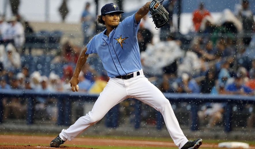 Tampa Bay Rays starting pitcher Chris Archer winds up to deliver to the Baltimore Orioles in the first inning of a spring training baseball game as rain begins to fall, Saturday, March 19, 2016, in Port Charlotte, Fla. The game was cancelled due to heavy rain in the region. (AP Photo/Tony Gutierrez)